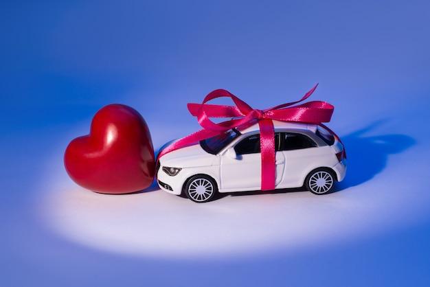 Profilseitennahaufnahmefoto eines weißen schönen spielzeugautos mit rosa schleifenband vorhanden mit rotem herz-valentinstag-konzept, das in der mitte des scheinwerferscheinwerfers lokalisiert auf blauem hintergrund steht