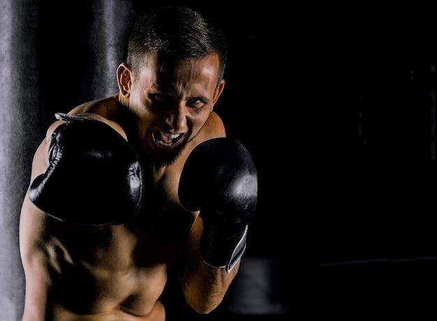 Profisportler der mixed martial arts steht in kampfhaltung und schlägt mit dem krim auf den feind ein. vorderansicht