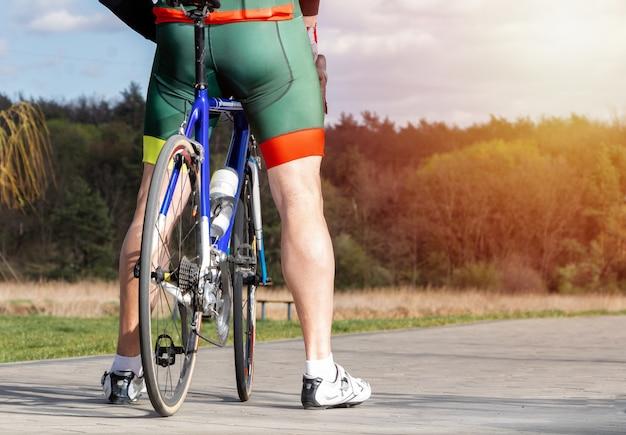 Profisportler in einer fahrraduniform steht auf einem fahrrad. aktiver lebensstil. radfahrer, der nach dem training auf einem fahrrad ruht.