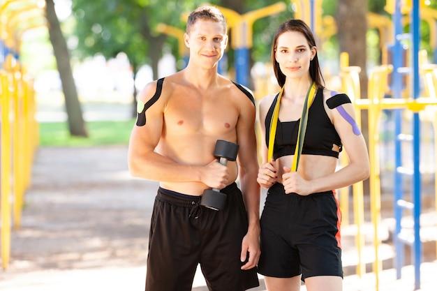 Profisportler, mann und frau mit kinesiologie-klebeband am körper