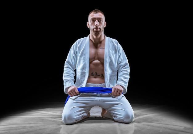 Profisportler sitzt im fitnessstudio in einem kimono mit blauem gürtel. konzept von karate, jiu-jitsu, sambo, judo. gemischte medien