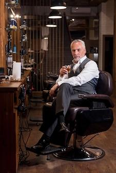 Profitables geschäft. attraktiver bärtiger mann, der auf speziellem sessel mit whiskyglas und zigarre am friseursalon sitzt.