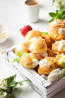 Profiteroles (choux à la crème) - französische choux-gebäckbällchen mit hüttenkäse und sahne mit erdbeere, minze und tasse kaffee.