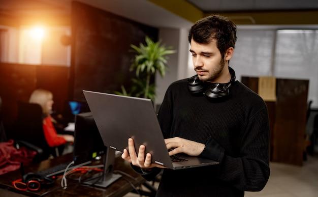 Programmierer im büro. start-up unternehmen. software-ingenieur, der mit laotop in den händen steht. entwicklungskonzept.