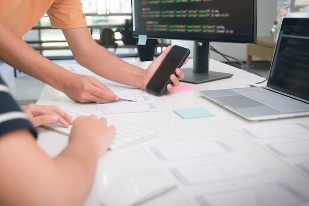 Programmierer und ux ui-designer arbeiten in einer softwareentwicklungs- und codierungstechnologie. app design und programmierung entwicklungstechnologie.