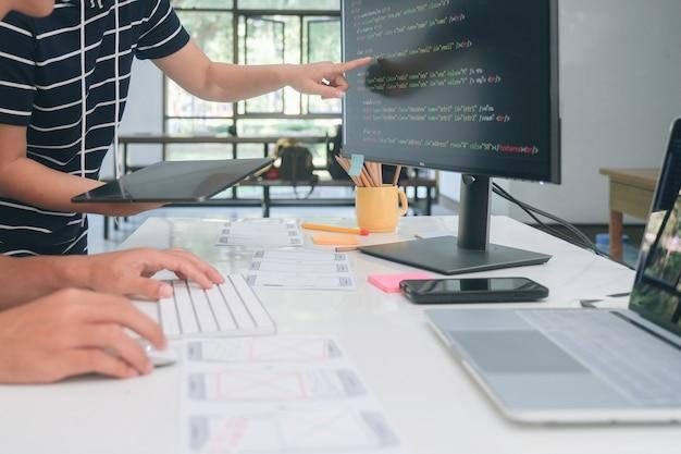 Programmierer und ux ui-designer arbeiten in einer softwareentwicklungs- und codierungstechnologie. entwicklungstechnologie für das design und die programmierung von mobilgeräten und websites.