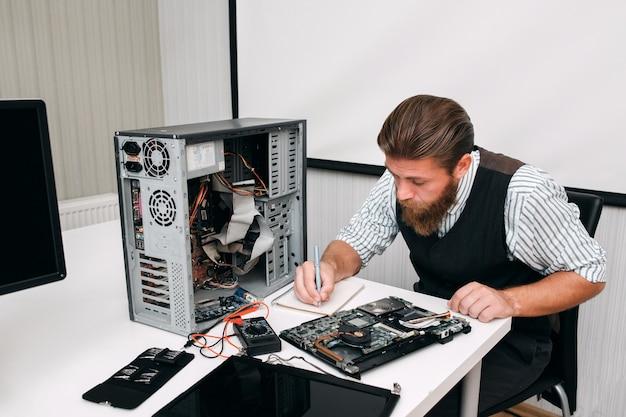 Programmiererinventarisierung elektronischer geräte. ingenieur, der in der nähe sitzt, zerlegt die cpu und macht sich notizen. reparatur, entwicklung, konzept prüfen