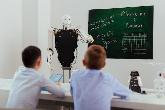 Progressive bildung. intelligenter selbstfahrender roboter, der nahe der tafel steht, während er eine lektion durchführt