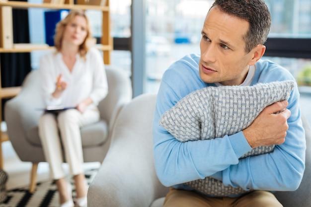 Progressive depression. trauriger depressiver erwachsener mann, der ein kissen hält und sich nervös fühlt, während er eine depression hat