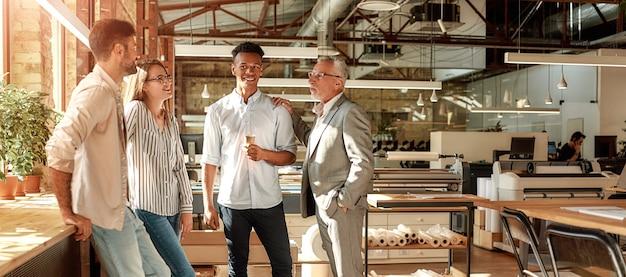 Projekt fertige geschäftsleute, die kaffeetassen halten und mit einem lächeln über etwas sprechen, während sie