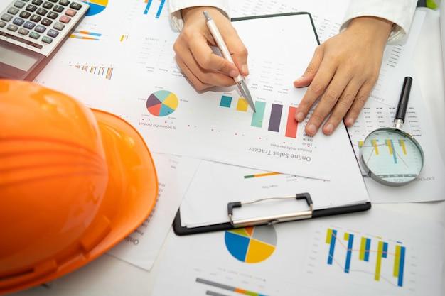 Projektabrechnung des architekten oder ingenieurs mit grafik im büro.