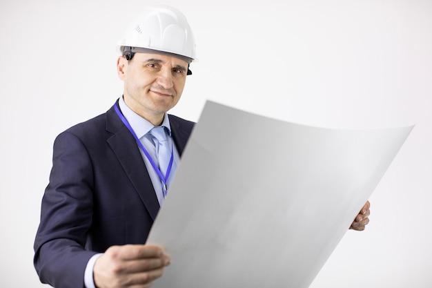 Projektleiter im schutzhelm, der blaupause hält und kamera mit lächeln betrachtet