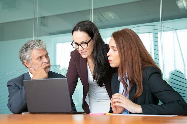 Projektmanager zeigt präsentation auf laptop für kollegen.