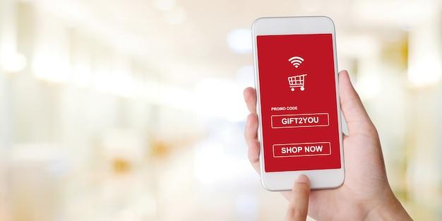 Promo-code auf dem handy-bildschirm für online-rabatt einkaufen, hand hält smartphone, um verkaufsgutschein auf blur store zu bekommen