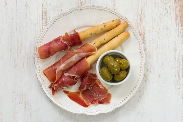 Prosciutto mit oliven auf weißer platte