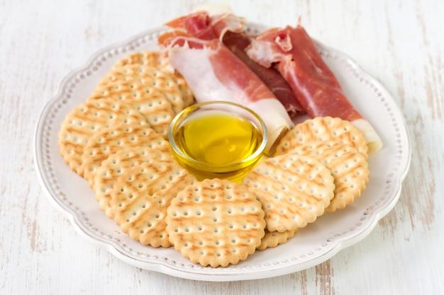 Prosciutto mit toast und olivenöl auf platte