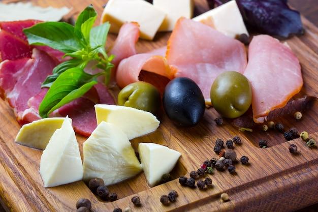 Prosciutto- und mozzarella-scheiben mit oliven und gewürzen