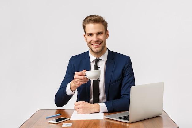 Prost. angenehmer erfolgreicher, schöner geschäftsmann mit dem blonden haar, bart, sitzendem büro, erhöhungskaffeetasse und der lächelnden unterhaltung mit teilhaber, mitarbeitern, arbeitend mit laptop und dokumenten