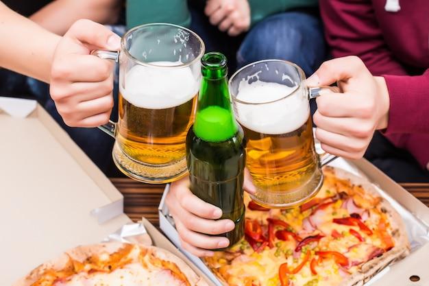 Prost. draufsicht auf männer mit gläsern bier und pizza