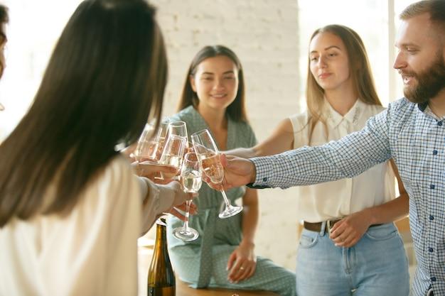 Prost leute, die mit wein oder champagner anstoßen fröhliche fröhliche freunde feiern