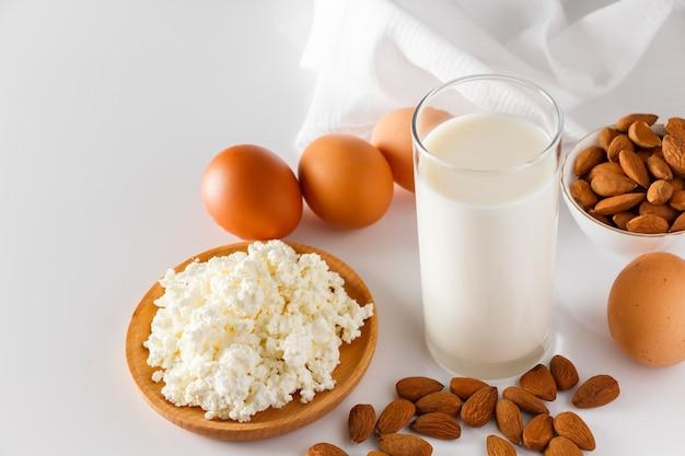 Proteinreiche lebensmittel auf weißem hintergrund hüttenkäse eier nüsse gesunde lebensmittel für eine ausgewogene ernährung