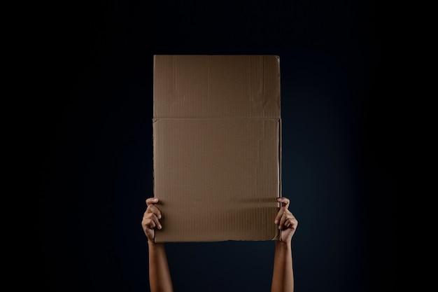 Protest-, mob- oder ausdruckskonzept. person hob ein leeres wellpappe.