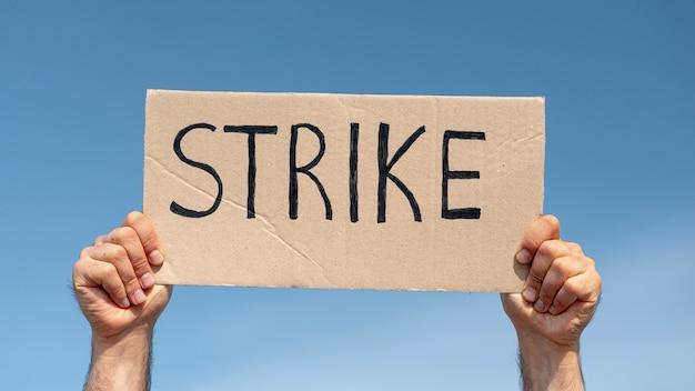 Protestierender, der brett mit streik hält
