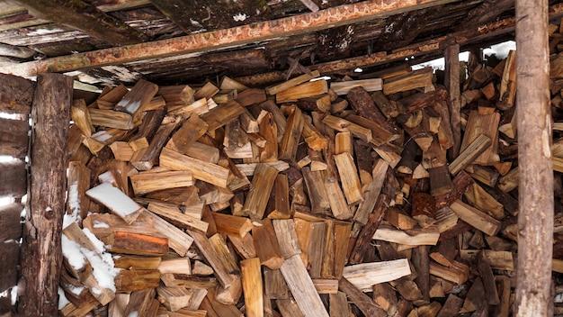 Protokollierung im dorf. gehackte stämme unter einem baldachin im winter. naturholzhintergrund.