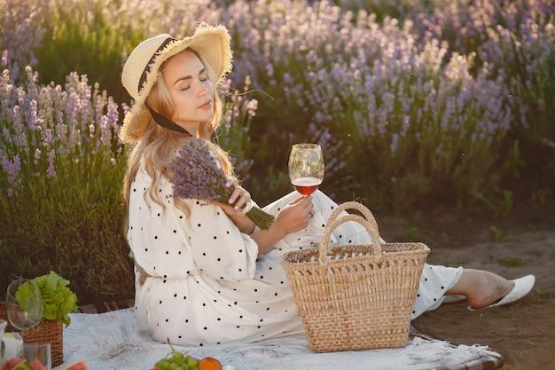 Provence frau, die im lavendelfeld entspannt. dame in einem picknick. frau mit strohhut.