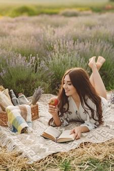Provence frau, die im lavendelfeld entspannt. dame in einem picknick.