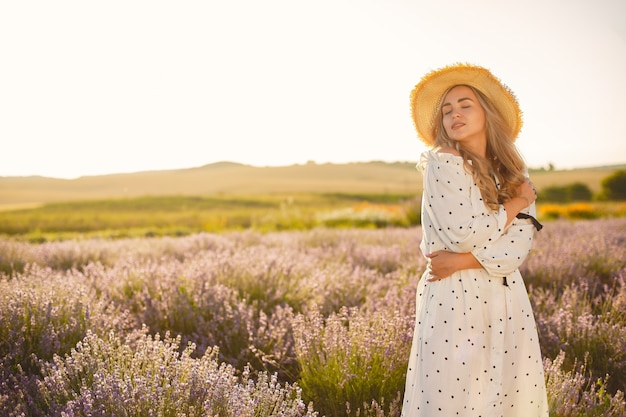 Provence frau, die im lavendelfeld entspannt. dame in einem weißen kleid. mädchen mit einem strohhut.