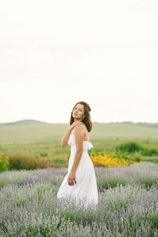 Provence frau, die im lavendelfeld entspannt. dame in einem weißen kleid. mädchen mit tasche.