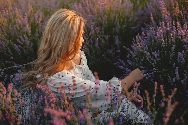 Provence frau, die im lavendelfeld entspannt. dame in einem weißen kleid.