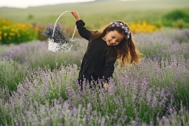 Provence kind, das im lavendelfeld entspannt. kleine dame in einem schwarzen kleid. mädchen mit tasche.