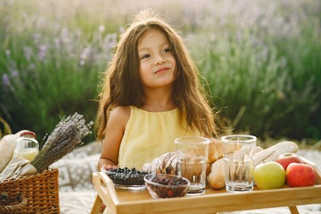 Provence kind, das im lavendelfeld entspannt. kleines mädchen in einem picknick.