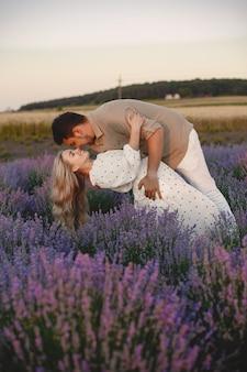 Provence-paar, das sich im lavendelfeld entspannt. dame in einem weißen kleid.