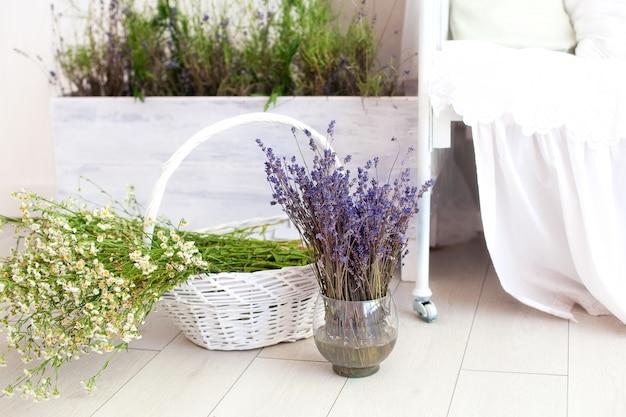 Provence, rustikaler stil, lavendel! ein großer korb mit feldgänseblümchen und eine lavendelvase stehen auf dem boden im schlafzimmer. aromatherapie. das konzept der sommerferien auf dem land.