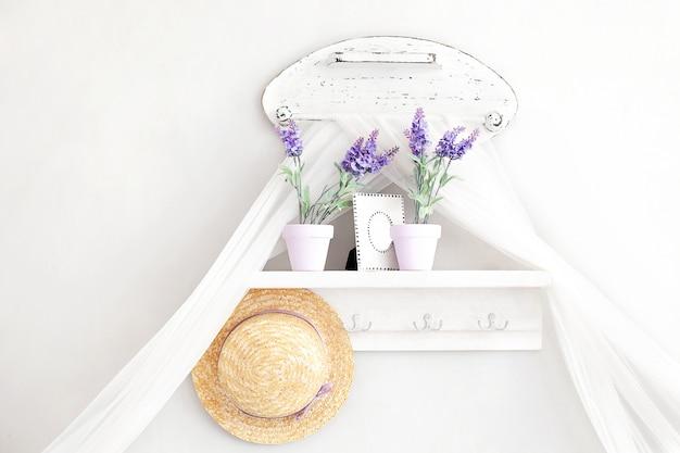 Provence, rustikaler stil. shabby chic im provenzalischen stil. dorf, landhaus. regal für hüte, haushaltsgegenstände im sanften französischen stil auf weiß. schlüsselhalter mit lavendeltöpfen. dekor