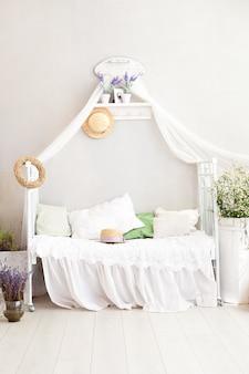 Provence-stil, rustikaler stil! shabby chic interieur girly schlafzimmer im provenzalischen stil. vintage zimmer interieur mit weißem schmiedeeisernen bett. lavendel, ein großer strauß feldgänseblümchen im schlafzimmer. dorf