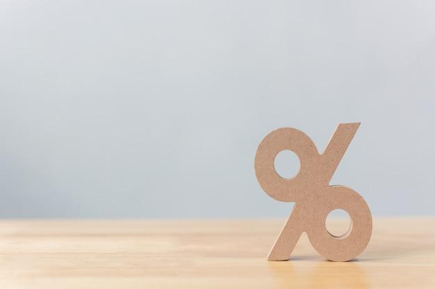 Prozentsatzzeichensymbolikone hölzern auf hölzerner tabelle mit weißem hintergrund