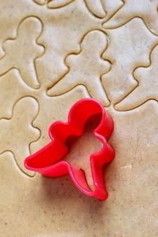 Prozess der behandlung von lebkuchenmannplätzchen, benutzen roten lebkuchenmann-formausschnitt-lebkuchenteig auf backpapier um bunte ausstechformen auf weißem holztisch. ansicht von oben