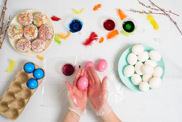Prozess der färbung von eiern für ostern in blauen und roten farben. eine frau in handschuhen malt eier mit farbstoff aus einem glas, draufsicht, weidenzweigen und buntem federdekor.