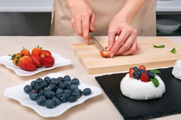 Prozess der herstellung von beerenkuchen. frauenhände schneiden erdbeeren, um das dessert zu dekorieren.
