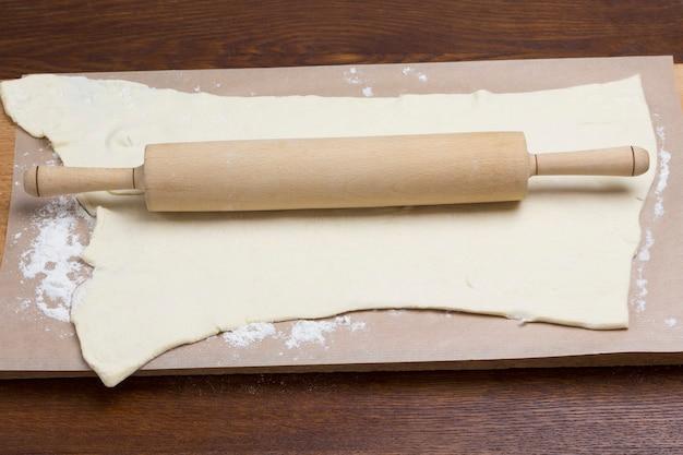 Prozess der herstellung von kochnudeln. nudelholz auf gerolltem teig