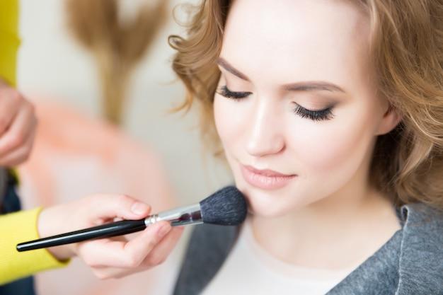 Prozess der herstellung von make-up. maskenbildner arbeiten mit pinsel auf modellgesicht. porträt der jungen blonden frau im innenraum des schönheitssalons. ton auf die haut auftragen.