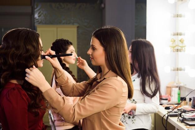 Prozess der herstellung von make-up. maskenbildner arbeiten mit pinsel auf modellgesicht. porträt der jungen frau im innenraum des schönheitssalons.