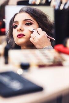 Prozess der herstellung von make-up. maskenbildner arbeitet mit pinsel auf dem gesicht des models.