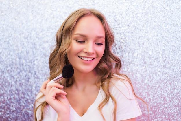 Prozess der herstellung von make-up. maskenbildner, der mit pinsel auf modellgesicht arbeitet. porträt der jungen blonden frau im innenraum des schönheitssalons. ton auf die haut auftragen.