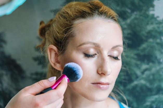 Prozess der herstellung von make-up. maskenbildner mit pinsel auf modell gesicht aufgetragen. porträt der jungen ingwerfrau im schönheitssalon. hand des make-up-meisters mit pinsel machen perfekte haut und farbe lidschatten