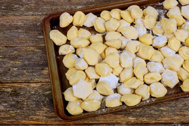 Prozess der herstellung von selbst gemachten pelmeni mehlklößen auf hölzernem brett - traditionelle ukrainische küche.